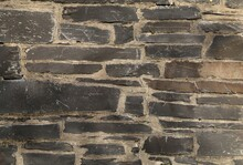 A Closeup View Of A House Wall Constructed Of Grey Welsh Slate With Non Uniform Stones And Mortar.