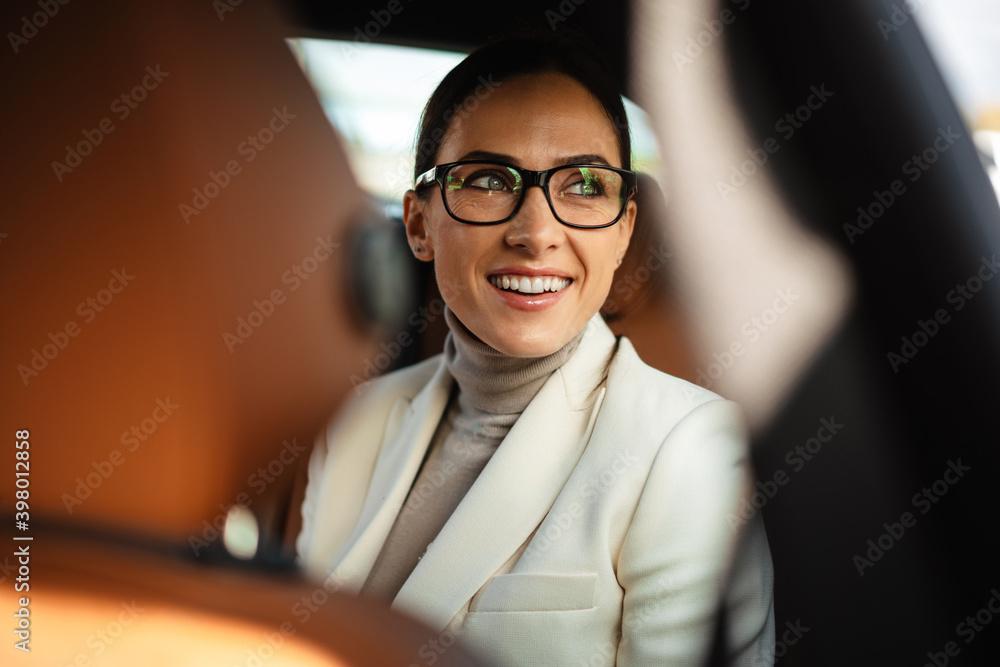 Fototapeta Positive pleased business woman sitting in a car