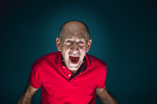 Screaming. Portrait Of Crazy Scared And Shocked Caucasian Man Isolated On Dark Background. Copyspace For Ad. Bright Facial Expression, Human Emotions Concept. Watching Horror On TV, Cinema.