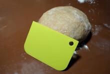 Green Rectangular Dough Scraper And Raw Round Brown Dough Made Of Rye Flour Water Butter And Egg Lies On A Brown Silicone Mat Side View . Baking At Home