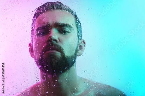 Canvastavla Portrait of handsome man through wet glass in neon light