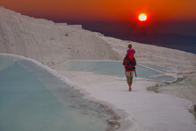 A Dad With His Daughter On His Shoulders Walks Along The Pamukkale Travertines During Sunset. Turkey