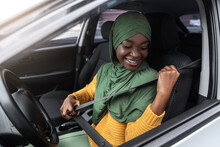 Safe Ride. African Woman In Hijab Sitting In Car Fastening Seat Belt