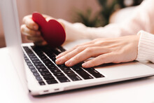 Close Up Of Woman Hands With Valentine Red Heart Card Typing At Laptop. Online Shopping At Christmas, Valentine Day Or Birthday Holidays. Freelance Girl Woking From Home Office