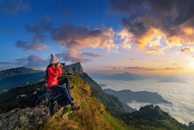 Traveller Sitting On The Rock And Holding Camera Take Photo At Doi Pha Mon Mountains In Chiang Rai, Thailand.