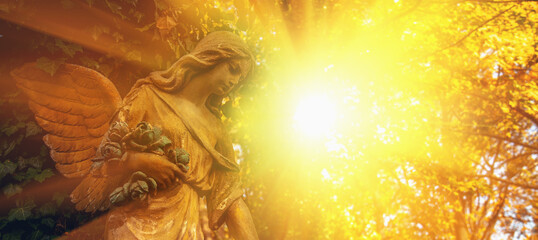 Guardian angel statue in sunlight. Horizontal image.