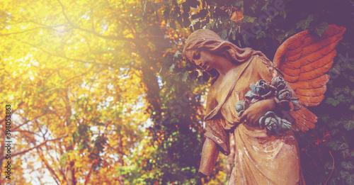 Stampa su Tela Fragment of ancient stone statue of beautiful guardian angel in sun rays