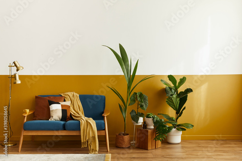Fototapeta Cozy interior with stylish velvet sofa, wooden cube, carpet, decoration, copy space, a ot of plants and elegant personal accessories. Modern living room in classic house. Template. obraz na płótnie