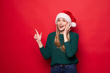 Young Woman Wearing Christmas Hat Smiling Happy Pointing With Hand And Finger To The Side On Red Background