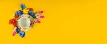 Yellow Background And Saucer For An Empty Cup Of Tea Surrounded By Flowers, Copy Space, Flat Ley, Top View Banner