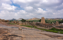 Hampi, Karnataka, India - November 4, 2013: Virupaksha Temple Complex. Slanted Rock Plateau Leading To Landscape With Said Temple Under Blue Cloudscape, Some Green Forests And Hill On Horizon.