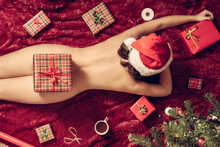 Top View Of Naked Woman In Santa Claus Hat Lying On Fluffy Plaid Near Christmas Tree On With Christmas Gift Box On Buttocks. Concept. Flat Lay