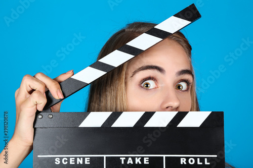 Beautiful girl with clapperboard on blue background Fotobehang