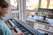 Homeschool European Young Boy Learning Piano From Computer Connecting To Internet Music Online Class By School Teacher. New Normal Lifestyle And Education, Student Study At Home Concept.