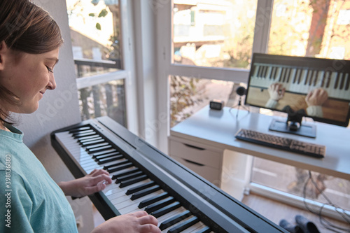Obraz na płótnie Homeschool European young boy learning piano from computer connecting to internet music online class by school teacher