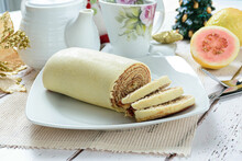 Bolo De Rolo (roll Cake) Sliced Next To A Christmas Decoration. Traditional Brazilian Candy, Side View.