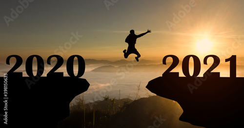 Abstract silhouette of man jump to New year 2021 at sunrise with mist cover moutain, Happy New year 2021 concept
