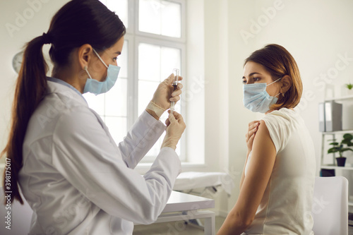 Fototapeta Nurse drawing medication out of vial before administering antiviral vaccine to young woman obraz
