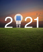2021 White Text And Light Bulb With Solar Cell Inside On Green Grass Field Over Over Sunset Sky With Birds, Happy New Year 2021 Ecological Cover Concept