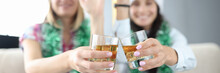 Women With New Year's Decorations And In Santa Hats Hold Glasses Of Alcohol In Their Hands Close-up And Waving. Happy New Year Greetings Online Concept.