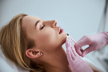 Professional Cosmetologist Injecting A Dermal Filler Into The Patient Lips