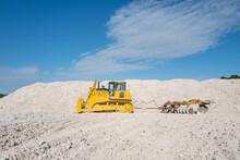 Yellow Bulldozer Moving Limestone In The Quarry. Faxe Kalkbrud, Denmark