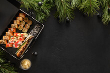 Food Delivery For Asian Sushi Set For Christmas Dinner Or New Year Party On Black Background. View From Above. Flat Lay Style. Copy Space.