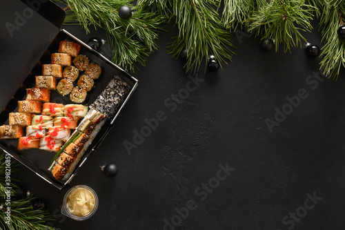 Fototapeta Food delivery for asian sushi set for Christmas dinner or New Year party on black background