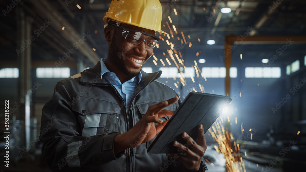 Fototapeta Professional Heavy Industry Engineer/Worker Wearing Safety Uniform and Hard Hat Uses Tablet Computer. Smiling African American Industrial Specialist Standing in a Metal Construction Manufacture.