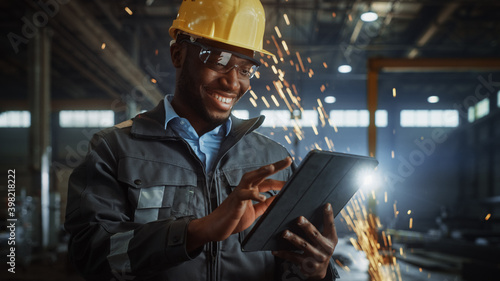 Fotografie, Obraz Professional Heavy Industry Engineer/Worker Wearing Safety Uniform and Hard Hat Uses Tablet Computer
