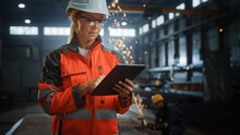 Professional Heavy Industry Engineer/Worker Wearing Safety Uniform And Hard Hat Uses Tablet Computer. Serious Successful Female Industrial Specialist Standing In A Metal Construction Manufacture.
