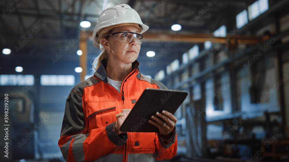 Fototapeta Professional Heavy Industry Engineer/Worker Wearing Safety Uniform and Hard Hat Uses Tablet Computer. Serious Successful Female Industrial Specialist Walking in a Metal Manufacture Warehouse.