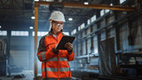 Professional Heavy Industry Engineer Worker Wearing Safety Uniform and Hard Hat, Using Tablet Computer. Serious Successful Female Industrial Specialist Walking in a Metal Manufacture Warehouse.