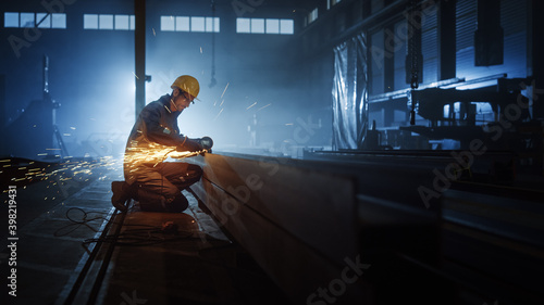 Obraz na plátne Heavy Industry Engineering Factory Interior with Industrial Worker Using Angle Grinder and Cutting a Metal Tube