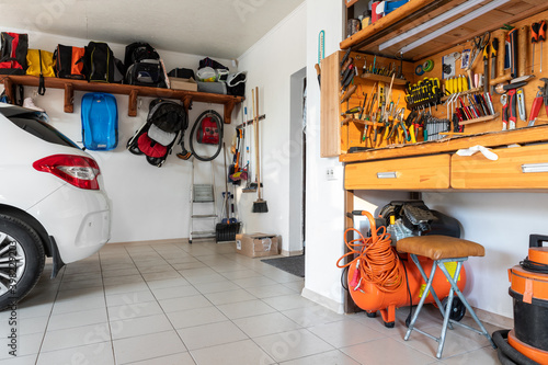 Fotografija Home suburban car garage interior with wooden shelf, tools equipment stuff storage warehouse on white wall indoor