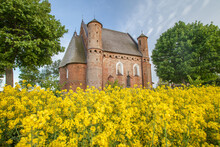 Church Of St. Michael The Archangel In Synkovichi Village, Belarus, Medieval Castle In A Yellow Rapeseed Field.
