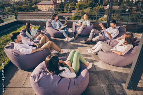 Obraz Nice attractive stylish partners leaders company unity sitting in bag chairs discussing project development on roof outside outdoor sunny day - fototapety do salonu
