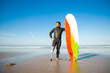 Leinwandbild Motiv Confident handicapped man standing on sea beach with board. Attractive brunette man with artificial leg wearing black wetsuit and looking at ocean. Physical disability and extreme sport concept