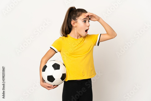 Fényképezés Little football player girl isolated on white background doing surprise gesture