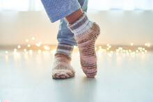 Female Legs Wearing Warm Winter Knitted Socks At Home