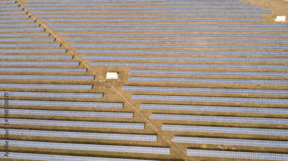 Fototapeta Aerial shot of photovoltaics solar farm. Solar farm power station from above. Ecological renewable energy.