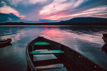 Wooden Boat On The Shore Of The Lake After Sunset With Purple Clouds