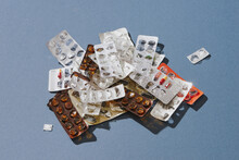 A Pile Used Blister Packs Of Pills On Blue Background.
