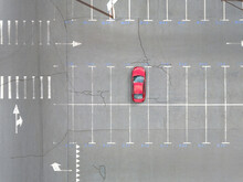 Single Red Car On An Empty City Parking. Top Aerial View.