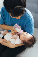 Asian Loving Mother Feed Her Cute Newborn Baby While Sitting On Sofa.