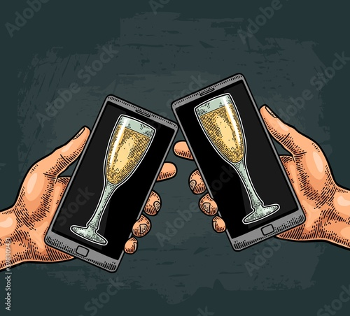 Fototapeta Male hands holding and clinking a modern mobile phone with glasses champagne obraz