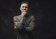 Portraif Of A Happy And Tattooed Hipster Person Dressed In Ragged Gray Shirt Posing In Dark Background With Hand Under His Chin.