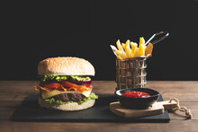 Hamburger Chips And Ketchup On Wooden Base On  Dark Background.
