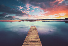Colorful Sunset Sunrise Dramatic Sky Above Wooden Boards Pier On Calm Water Of Lake, River. Nature, Peace Concept