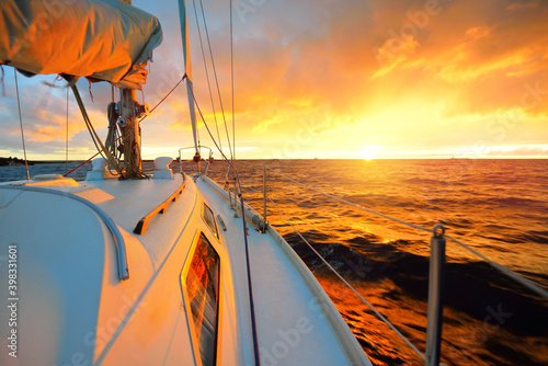 Obraz na plátne White yacht sailing in an open sea at sunset
